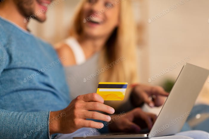 Unrecognizable Couple Using Laptop And Credit Card Sitting On Sofa