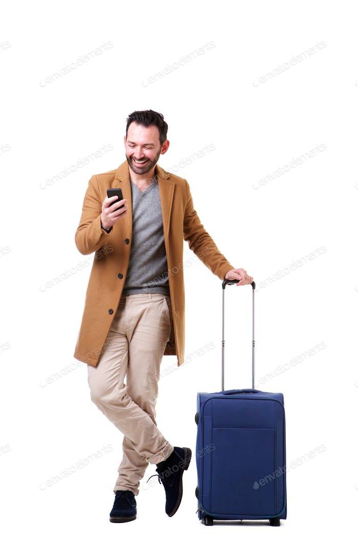Full length male traveler standing with mobile phone and suitcase against white background