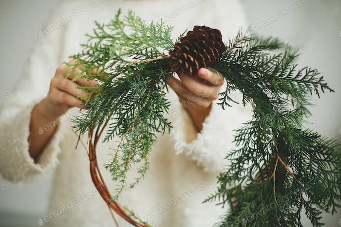 Деревенский рождественский венок в женских руках.