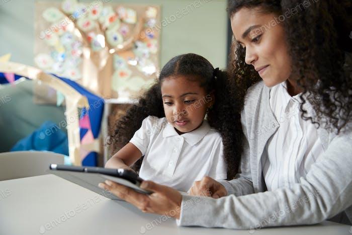 Schwarzes Schulmädchen in einer Säuglingsschule Lernen mit einer Lehrerin mit einem Tablet-Computer