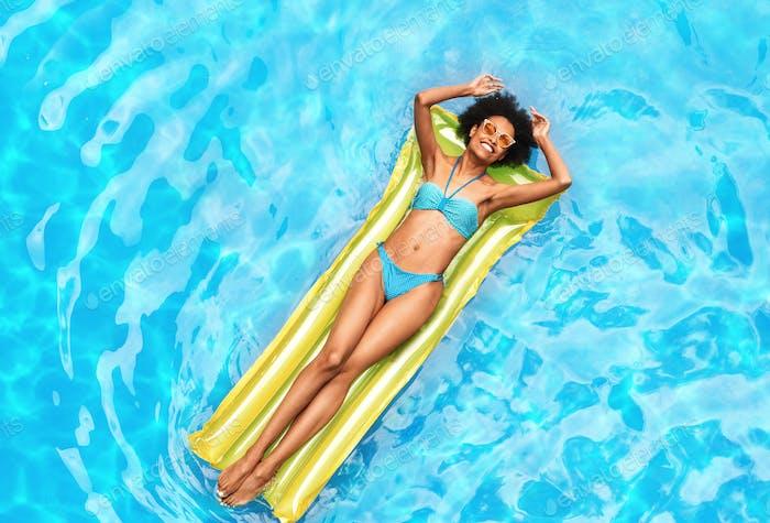 Sommerferien. Millennial Black Girl entspannt auf Lilo im Außenpool am sonnigen Tag, Draufsicht