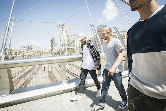 Group of young men walking along a bridge.
