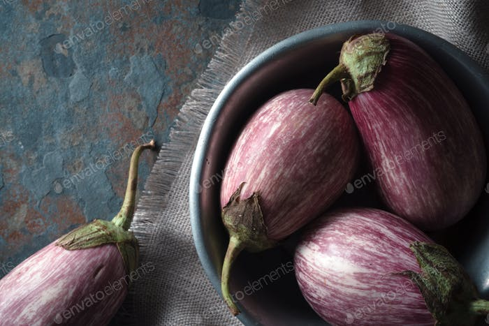 Eggplants in a tin bowl on a gray napkin on a blue stone
