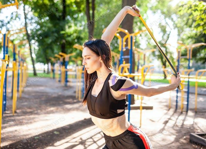 Professionelle Sportlerin posiert mit elastischen Bändern im Freien