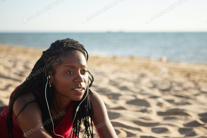 Sporty woman stretching on beach