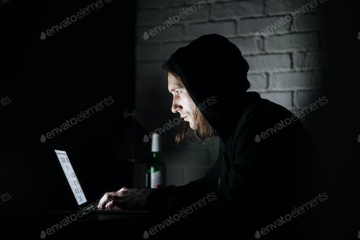 Man using laptop computer at home indoors at night