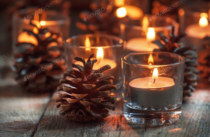 Christmas card with glowing small candle and fir cones