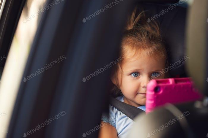 Young girl beobachten digital tablet in rücksitz auf auto reise