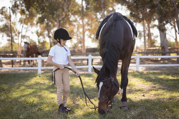 Full length of girl wearing helmet standing by horse