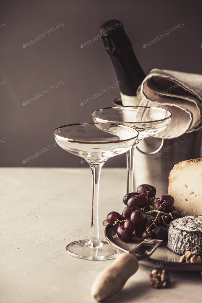 Champagne and cheese plate on concrete background