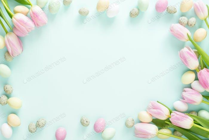 Osterrahmen aus Oster-Süßigkeiten-Eiern und Tulpen auf Türkis Hintergrund.