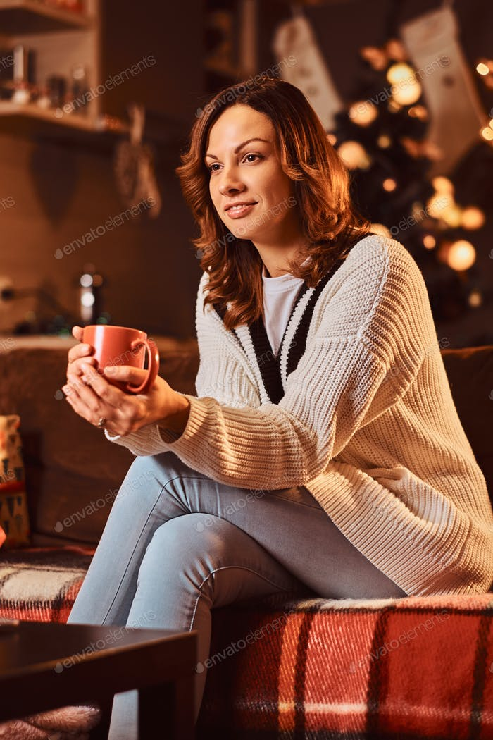 Happy relaxed woman in warm sweater holds mug with hot coffee in decorated room at Christmas time.