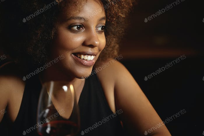 Headshot of beautiful stylish young African female with curlly hair siting at restaurant, holding gl