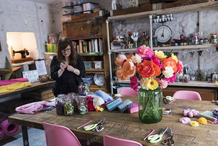 Woman standing in a workshop, bunch of colourful handcrafted fabric flowers in a vase on a table.