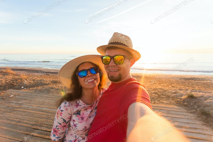 Happy traveling couple in love taking a selfie on phone with suitcases at the beach
