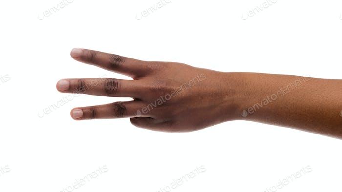 Weibliche Hand zeigt Nummer drei mit Finger auf weißem Hintergrund