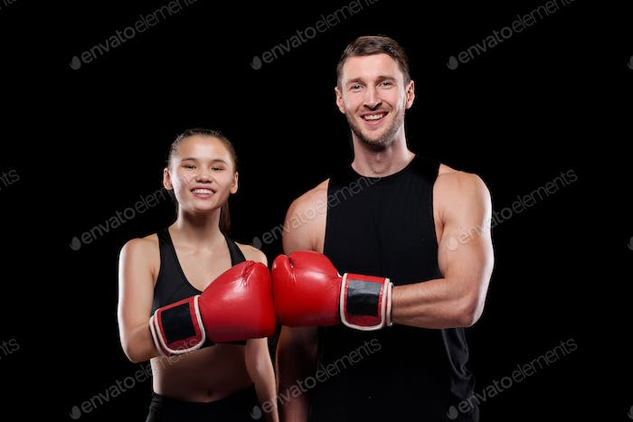 Happy man and woman in activewear touching each other hands in boxing gloves