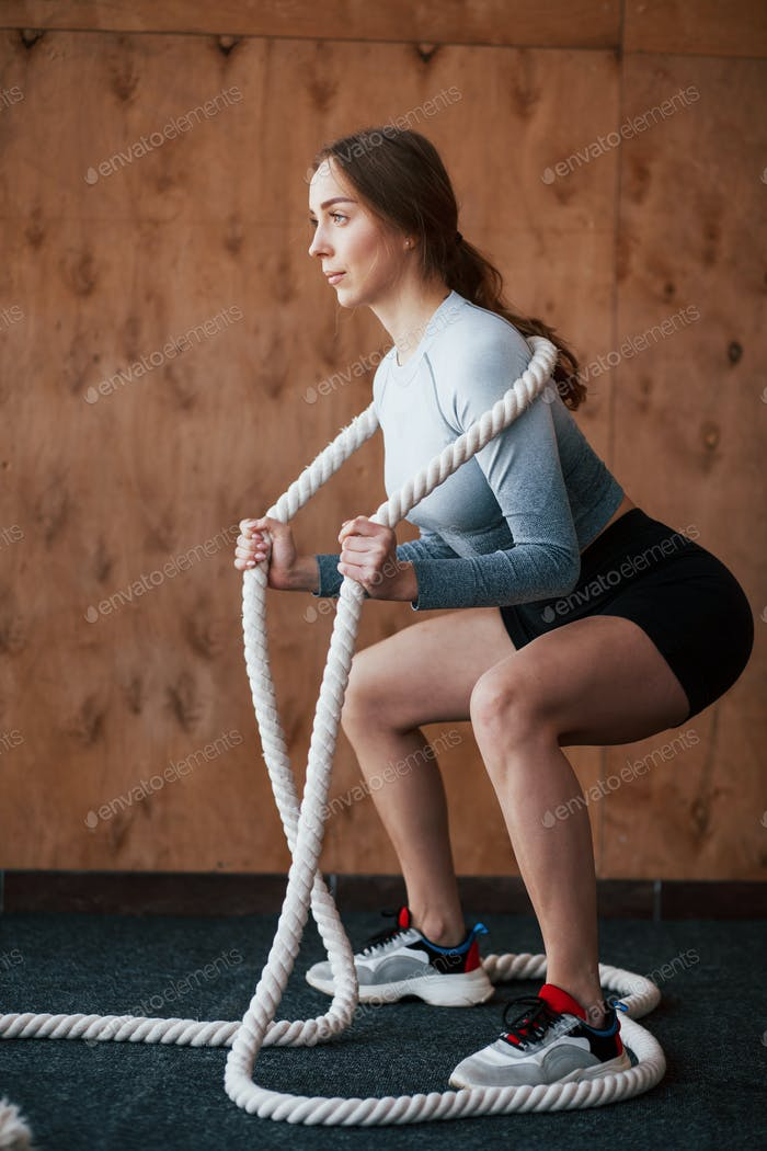 Squatting with a rope. Sportive young woman have fitness day in the gym at morning time