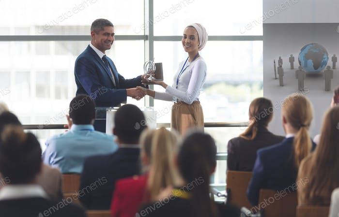 Businesswoman receiving award from businessman at a business seminar in office building