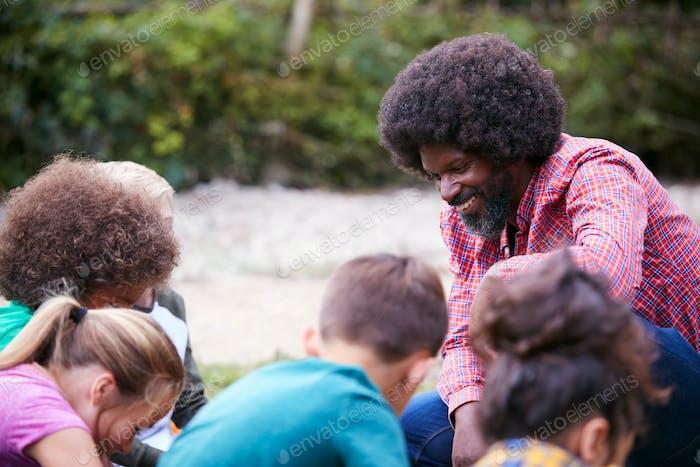 Teamleiter zeigt Gruppe von Kindern auf Outdoor-Camping-Trip Wie man Feuer macht