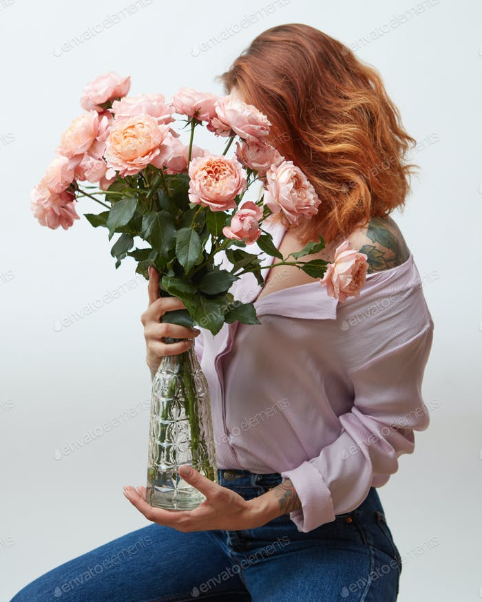 Red-haired girl with a tattoo and a beautiful pink bouquet of roses in a vase on a gray background