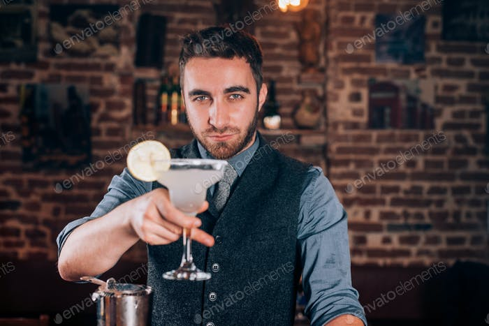 Cocktail details - smiling bartender serving drinks and fresh alcoholic beverages at bar