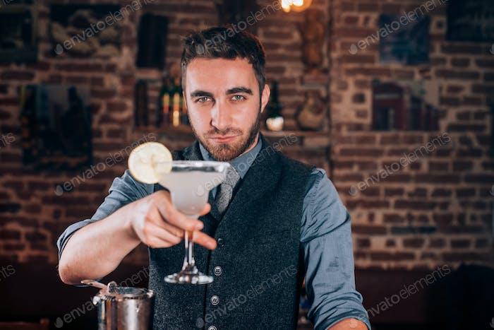 Cocktail-Details - lächelnder Barkeeper serviert Getränke und frische alkoholische Getränke an der Bar