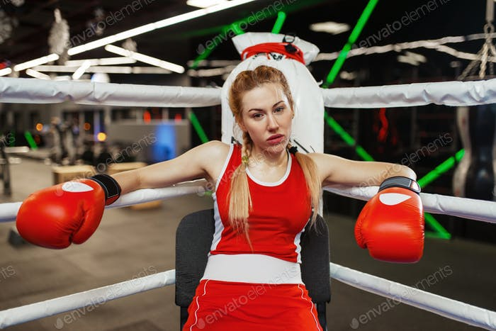 Woman in gloves sitting in corner of boxing ring