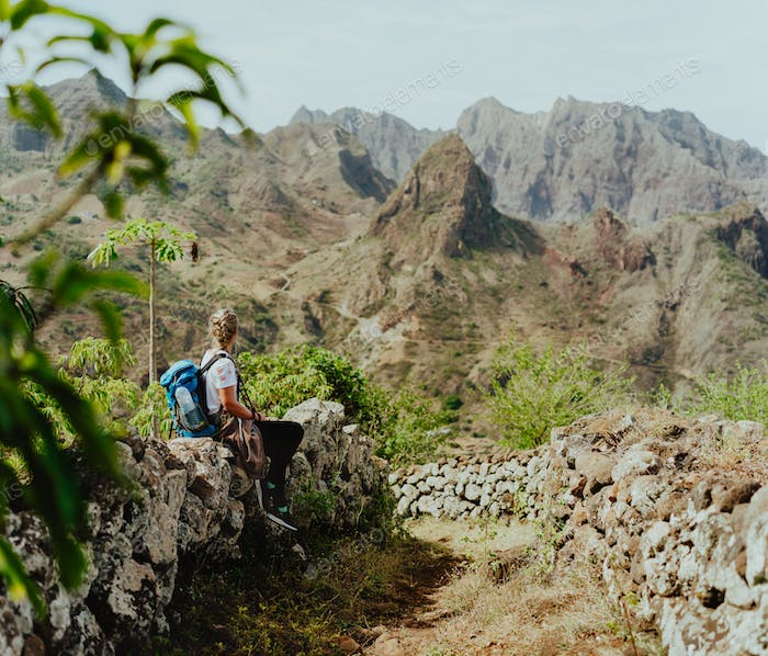 Santo Antao, Cape Verde. Woman tourist with backpack enjoying arid mountain ridge on hiking route to