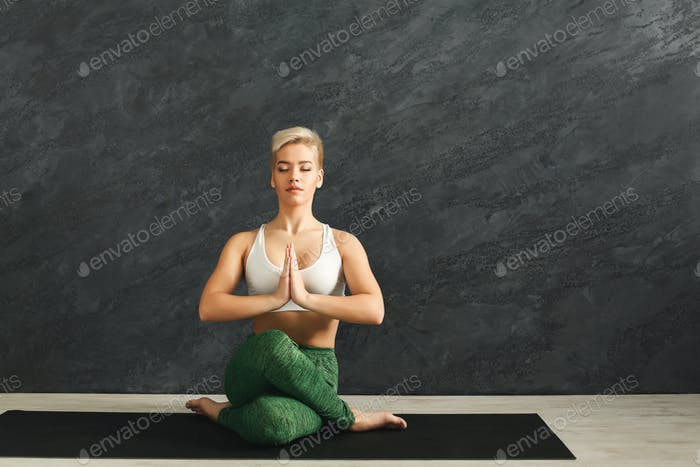 Woman training yoga in cow head pose in gym