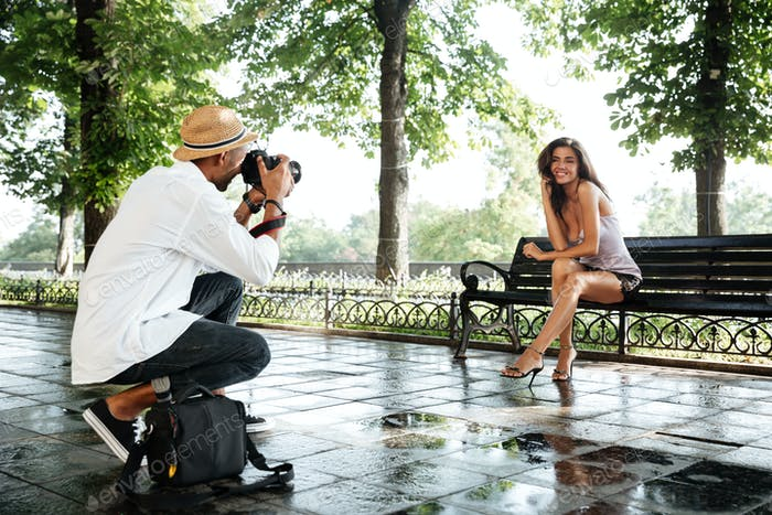 Photographer takes photo of young beautiful brunette woman in park