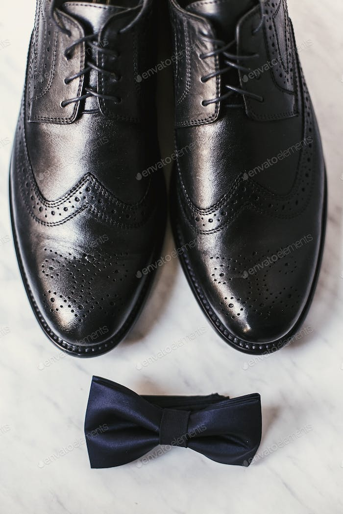 Stylish black shoes and navy bow tie on marble background