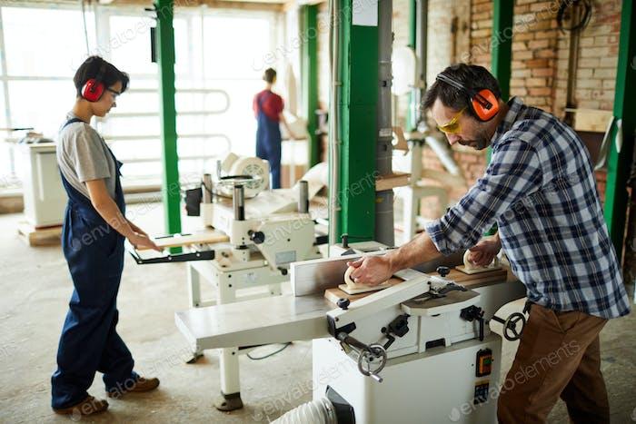Carpenter putting wooden plank on workbench