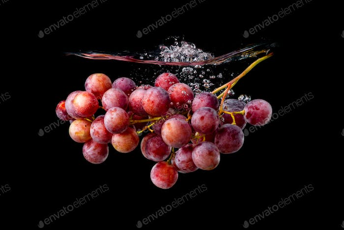 Isolated Red grapes splashing and sinking in water on black background