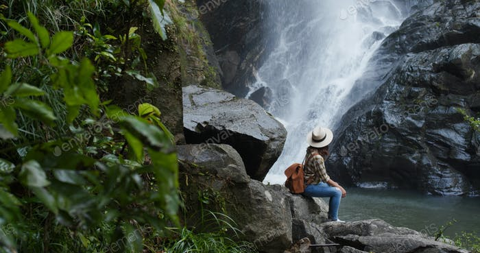 Woman enjoy the waterfall in forest