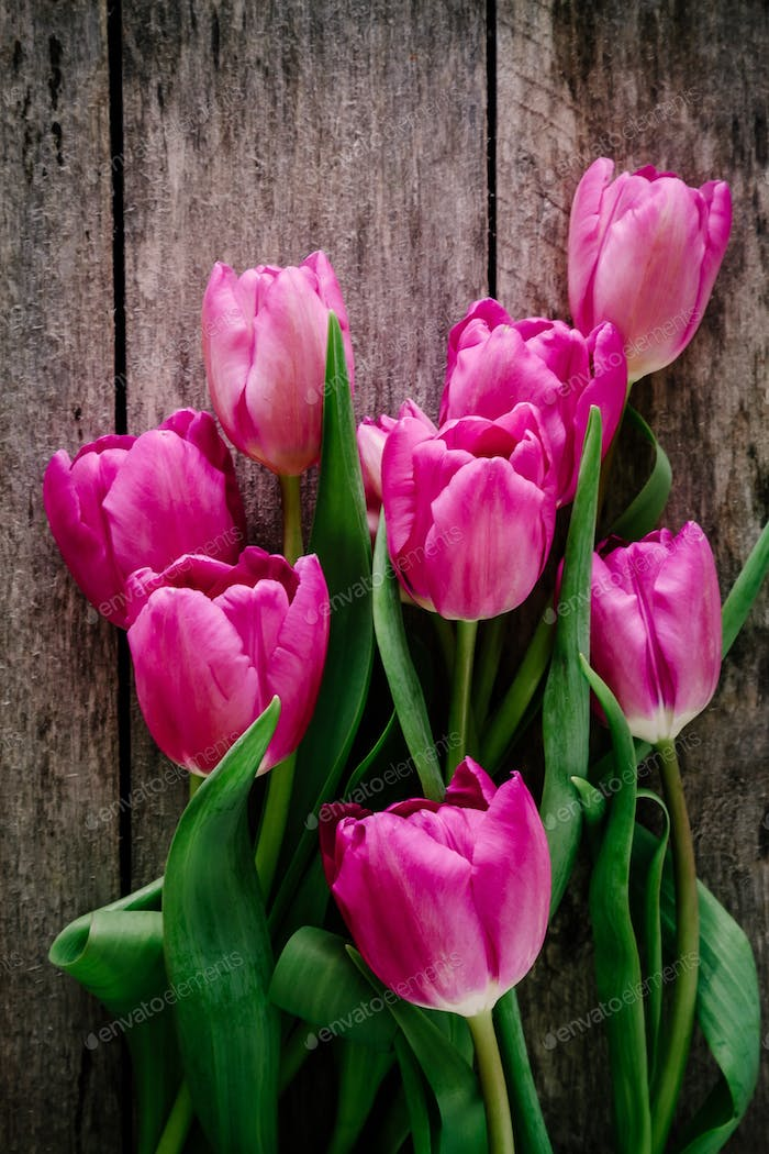 Pink tulips bouquet on a rustic wooden background. Mother's Day background.