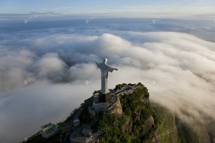 High angle view of colossal Christ Redeemer statue surrounded by clouds, Corcovado, Rio de Janeiro,