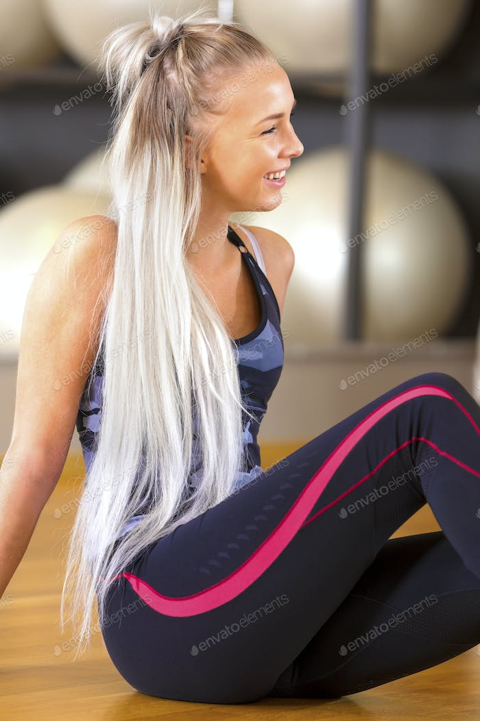 Smiling fitness woman sitting in workout outfit at the gym