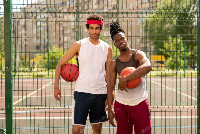 Small group of two young professional basketballers in activewear