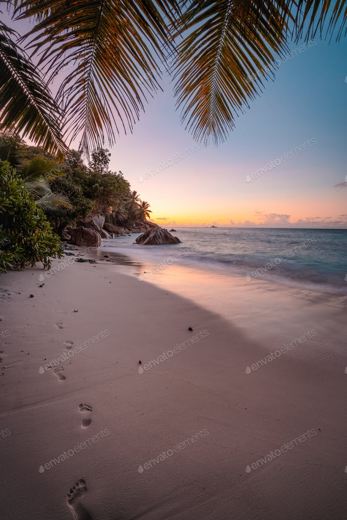 La Digue Island, Seychelles. Beautiful sunset lit colorful sky on exotic tropical sandy beach with