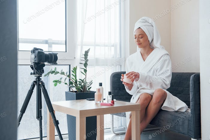 In front of camera on the tripod. Conception of fashion and skincare. Brunette girl uses cosmetics