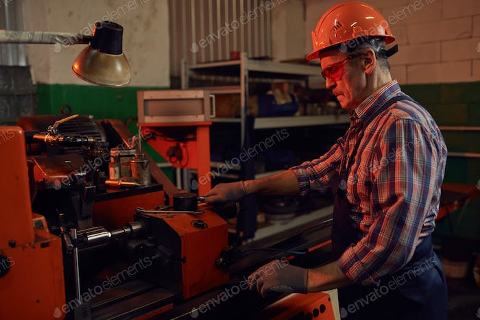 Engineer controlling the lathe