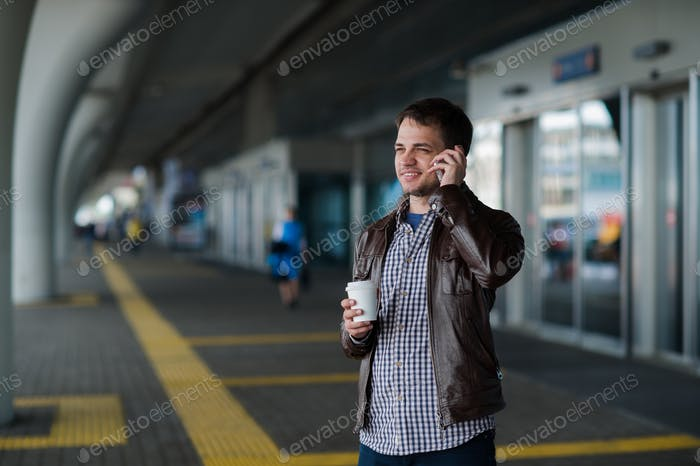 Close up portrait of a serious young man talking on mobile phone near the airport terminal with