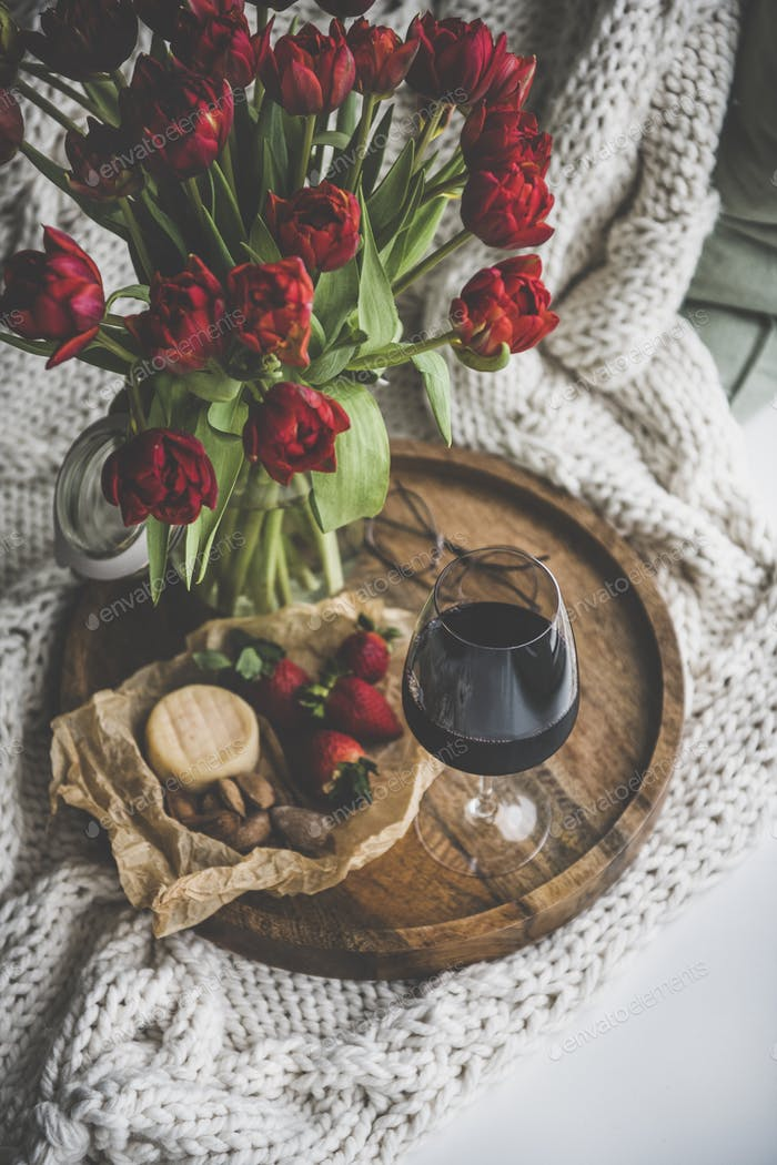 Glass of red wine, snacks and tulips on wooden board