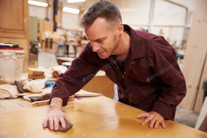Carpenter Finishing Wood In Carpentry Workshop
