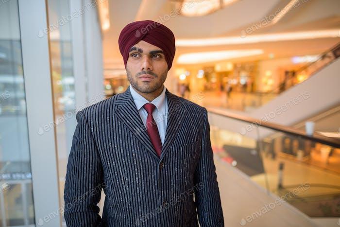 Porträt von indischen Geschäftsmann mit Turban Blick durch Fenster