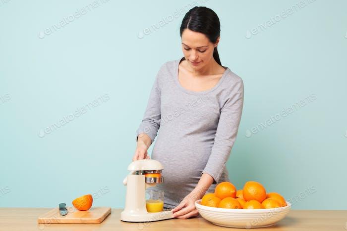Schwangere Frau macht frischen Orangensaft.