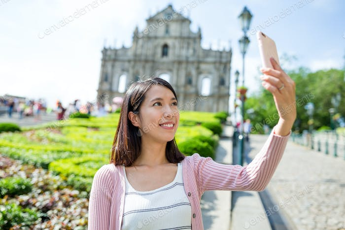 Young woman taking mobile phone in Macau city