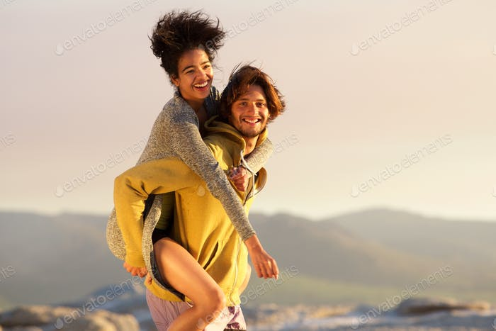 Smiling man giving piggyback to beautiful young woman
