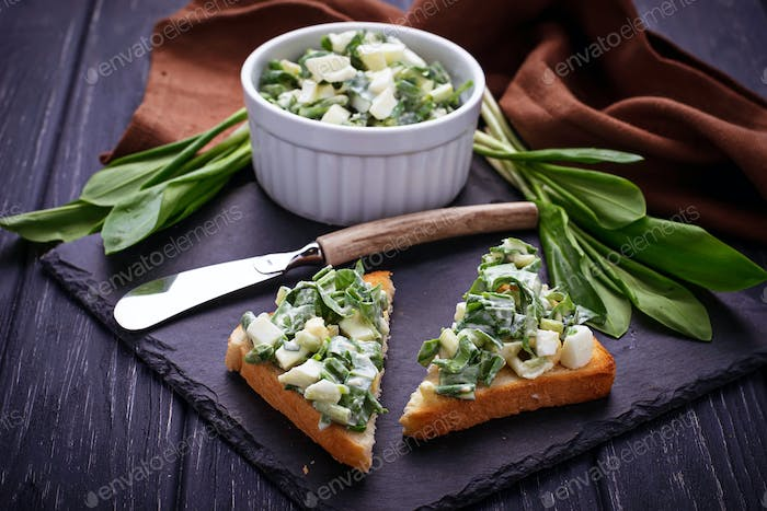 Bruschetta with ramson salad on slate background
